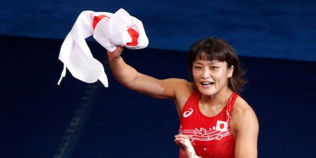 Kaori Icho, of Japan, celebrates after defeating Petra Maarit Olli, of Finland, during a women's freestyle...