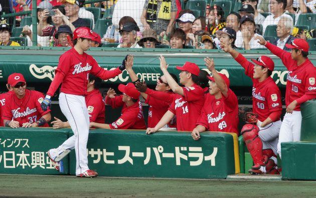 4回、スクイズを決め、ナインに迎えられる広島の野村(左手前)=18日、甲子園