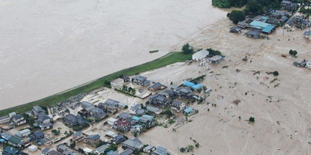 Floodwaters from the burst Kinugawa river (L) flow into a residential area (R) in Joso, Ibaraki Prefecture,...