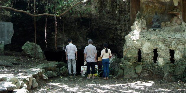 チビチリガマの洞窟入り口付近に祈りに訪れた人々=9月18日午後、沖縄県読谷村