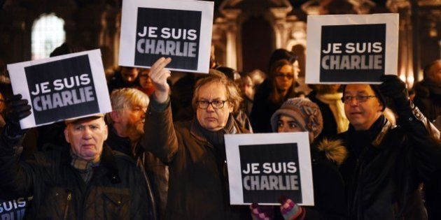People hold placards reading in French 'I am Charlie' during a gathering in front of the prefecture in...