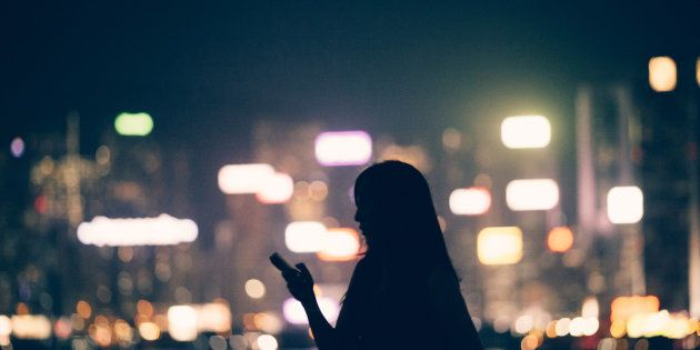 Silhouette of office lady using smartphone in