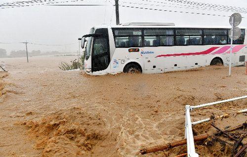 ●豪雨により国道386号に流れ込んだ水。その中を客を乗せたバスが走っていた=福岡県朝倉市須川、7月5日(朝日新聞)