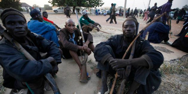 Vigilantes and local hunters armed with locally made guns gathered before they go on patrol in Yola,...