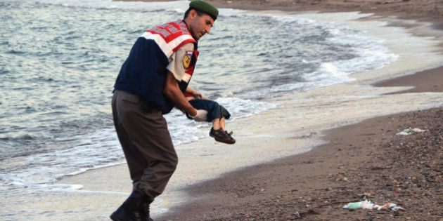 A paramilitary police officer carries the lifeless body of a migrant child after a number of migrants...