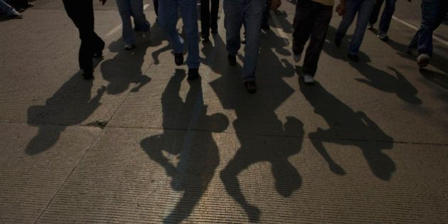 The shadow of electricians is cast on the road as they protest the government's shut down of a state-run...