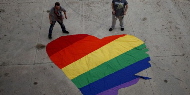 Fer Franco, 25, (R) and his partner Rafa Varon, 23, stand next to a heart-shaped cloth with rainbow colors...