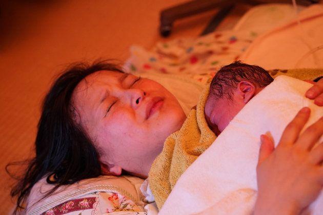 出産の余韻にまだ身も心も預けたままの女性。