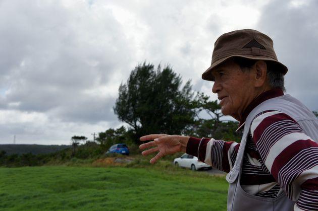 かつて米軍機が不時着した、自宅横の牧草地で話す渡久地さん=10月12日午後、沖縄県東村高江