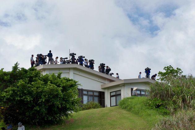 現場への立ち入りを制限され、規制線の外の民家の屋根から取材する報道関係者ら=10月12日、沖縄県東村高江
