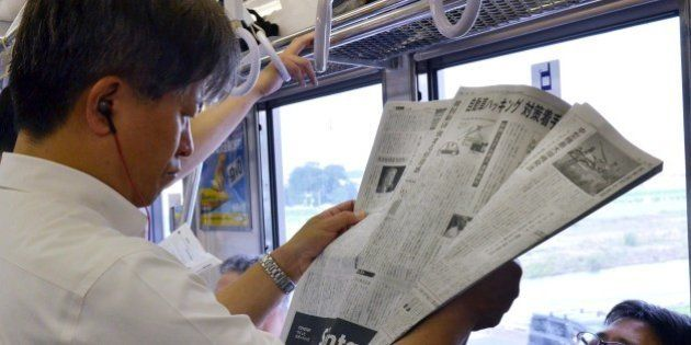 A man reads Japan's business daily newspaper, the Nikkei or Nihon Keizai Shimbun, in Tokyo on July 24,...