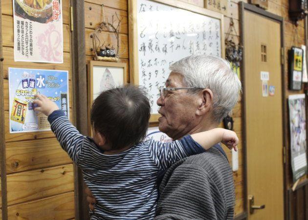 息子を抱っこする居酒屋の大将