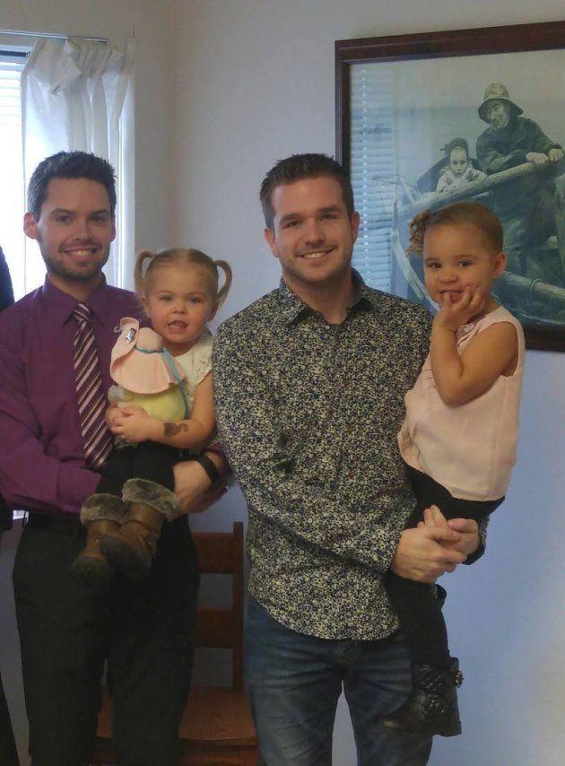 エミリーを抱くジョン(左)とブリンを抱くネイサン。エミリーの養子縁組が決まった日に撮影