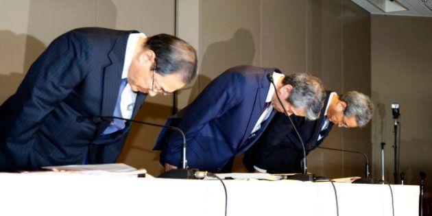 Toshiba Corp. CEO Hisao Tanaka, center, bows with chairman Tadashi Muromachi, left, and executive director...