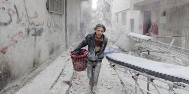 A boy carries his belongings at a site hit by what activists said was a barrel bomb dropped by forces...