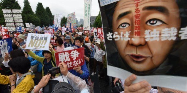 People shout slogans as they hold banners during an anti-government rally in front of the National Diet...