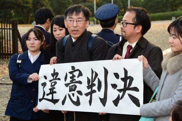 2015年12月、最高裁大法廷の違憲判決を受けて、取材に応じる作花和志弁護士=中央=