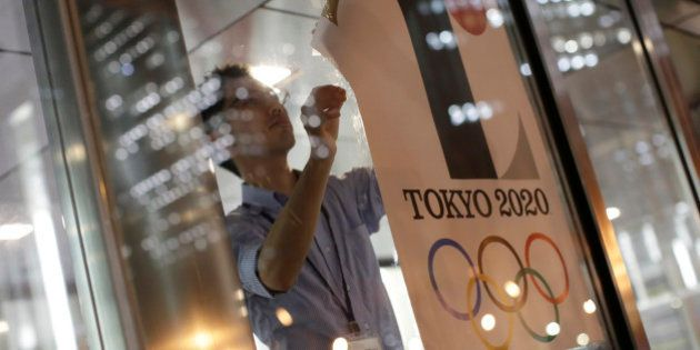 The poster with a logo of Tokyo Olympic Games 2020 is removed from the wall by a worker during an event...