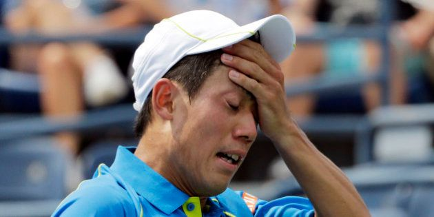 Kei Nishikori, of Japan, reacts after losing a point to Benoit Paire, of France, during the first round...