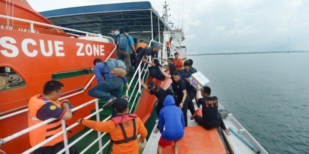 Members of an Indonesian search and rescue team prepare to set off to search at sea for missing AirAsia...