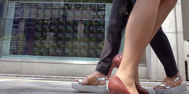 Women walk past an electronic stock indicator of a securities firm showing Tokyo's Nikkei 225 in Tokyo,...