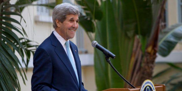U.S. Secretary of State John Kerry smiles as he arrive to speak to members of the media in Phnom Penh,...