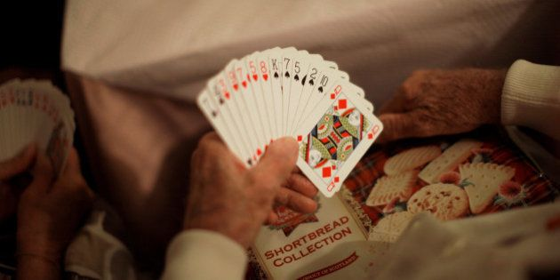 A British retiree living in Spain holds poker cards while playing bingo with other compatriots after...