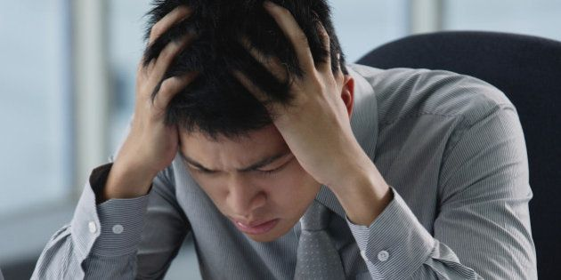 A man looks stressed as he works at his