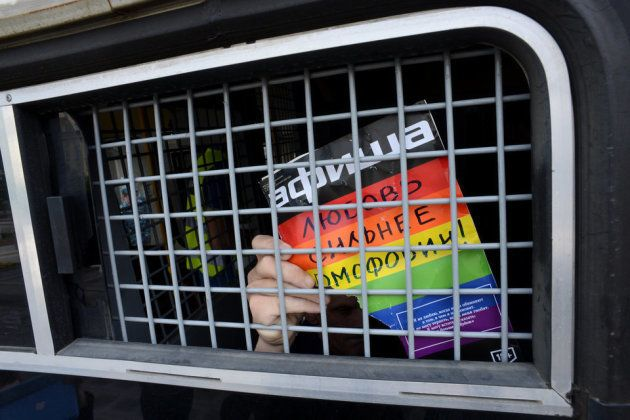 同性愛者の権利を求めるアクティビスト。モスクワの警察車内で手にしているサインには「愛は同性愛嫌悪より強い」と書かれている