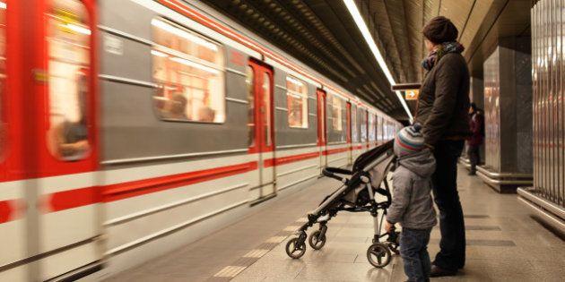 Family looking at train at subway station in