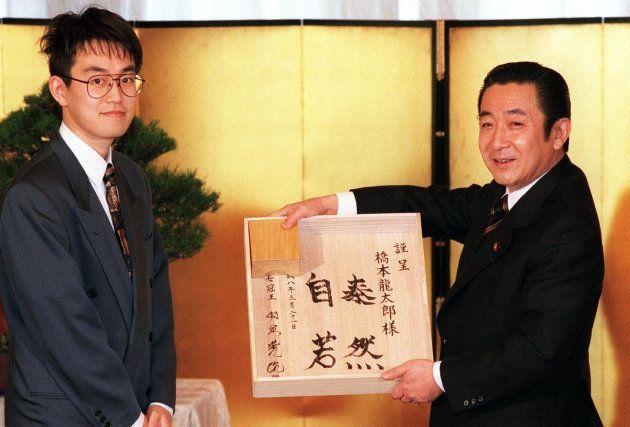 内閣総理大臣顕彰を受けた羽生善治名人(左)からサイン入りの将棋盤を贈られた橋本龍太郎首相(東京・首相官邸)