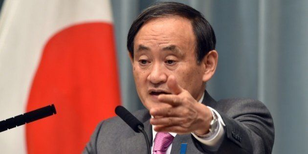 Japan's Chief Cabinet Secretary Yoshihide Suga points to a journalist at a press conference at the prime...