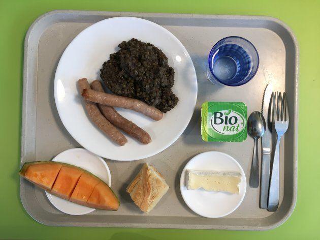 小学校学童給食...前菜・メイン・チーズ・デザートとパンが基本の構成。どんな料理も「一口味見をすること」を勧めるが、無理強いはしない。この日はソーセージとレンズ豆のメインに、メロンとカマンベールチーズ、チョコレートクリームがついた。