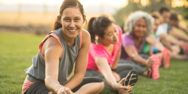 A group of adults attending a fitness class outdoors are doing leg stretches. The participants are arranged in a line. The focus is on a beautiful ethnic woman who is smiling toward the camera.