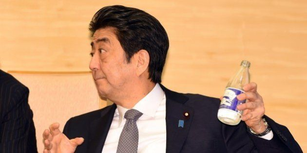 Japan's Prime Minister Shinzo Abe pours water into a glass while looking at visiting South African Deputy...