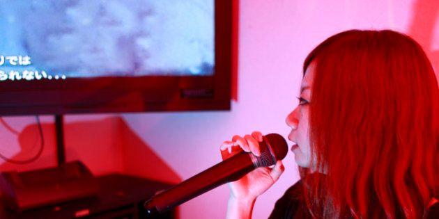 A young Japanese girl sings inside a Karaoke box, in Shibuya, Tokyo, Japan (Adobe