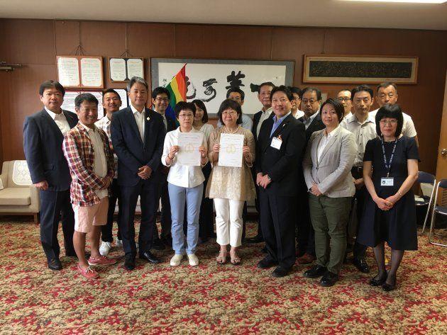 パートナーシップ制度の宣誓第1号となった大江千束さんと小川葉子さん。酒井直人中野区長、中野区議、「中野にじねっと」のメンバーらが駆けつけて2人を祝福した。