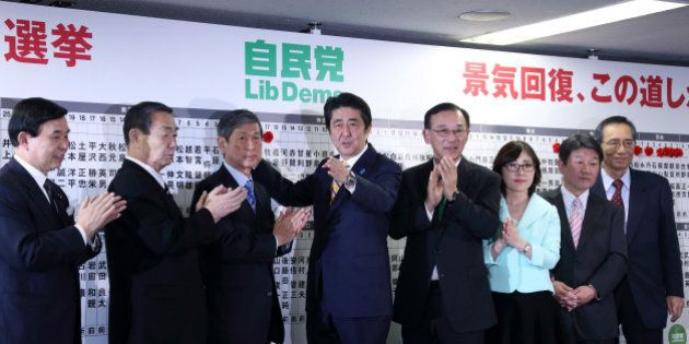 Shinzo Abe, Japan's prime minister and president of the Liberal Democratic Party (LDP), center, places...