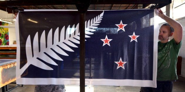 Factory workers Garth Price (R) and Andrew Smith (L) hang new designs of the national flag of New Zealand...