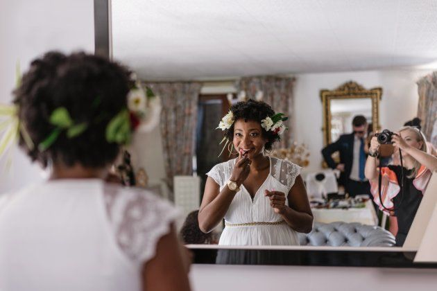 Reflection Of Bride Applying Lipstick While Standing In Front Of