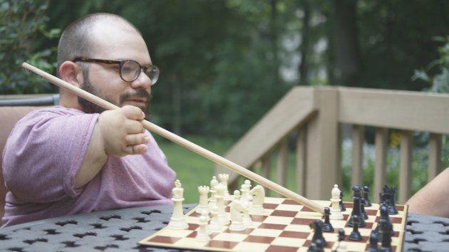 棒を使ってチェスの駒を動かすジョー