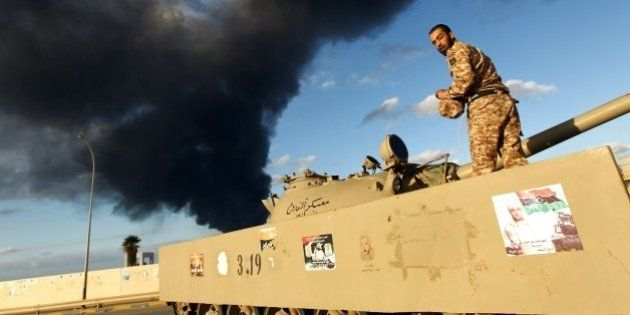 A member of the Libyan army stands on a tank as heavy black smoke rises from the city's port in the background...