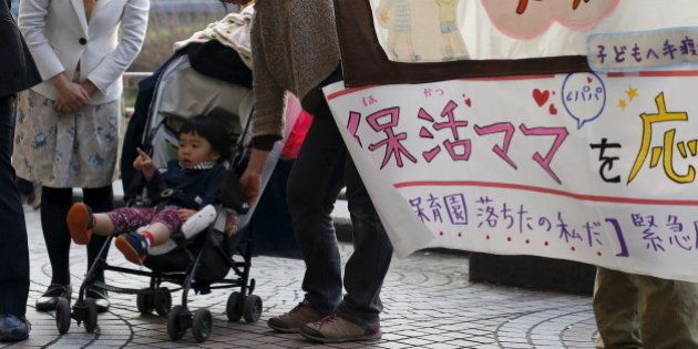 Two-year-old Amane Morohoshi sits in a baby stroller during a rally in support of mothers and fathers...