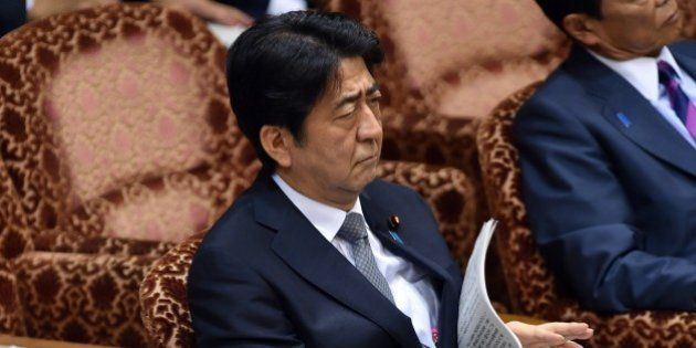 Japanese Prime Minister Shinzo Abe listens to a question by an opposition lawmaker at the Upper House's...