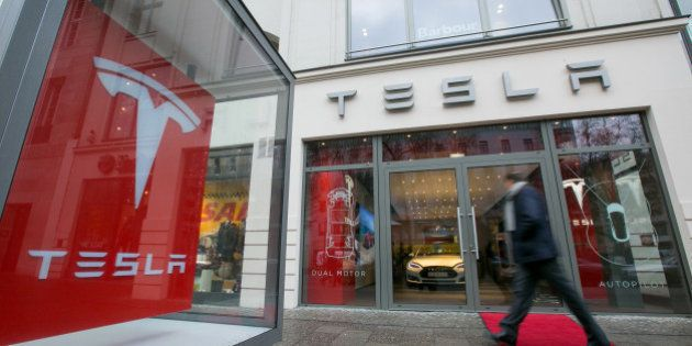 A pedestrian passes a Tesla Motors Inc. electric automobile showroom in Berlin, Germany, on Wednesday,...