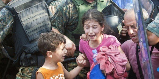 A young girl and boy cry as police block a group of migrants trying to cross the Macedonian-Greek border...