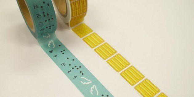 墨点字とひらがな併記のメッセージと点字ブロックがそれぞれプリントされたマスキングテープの2個セット。日本点字図書館などで買えます。