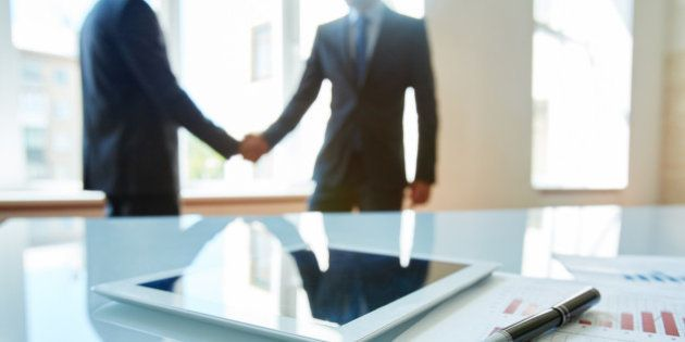 Business objects at workplace with handshaking partners on
