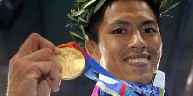 Athens, GREECE: Japan's Tadahiro Nomura shows his gold medal after winning the men's under 60 kg judo...