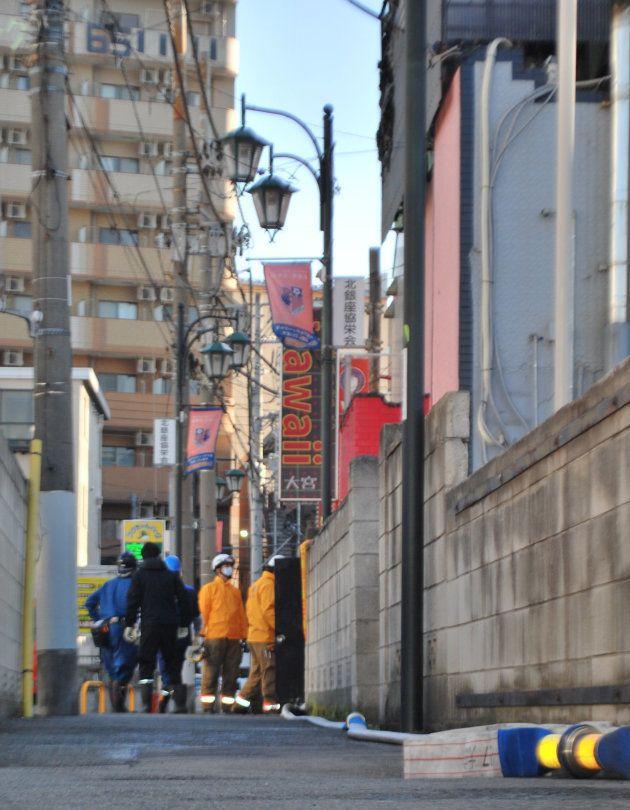 火災のあった風俗店を現場検証する警察と消防=18日、さいたま市大宮区